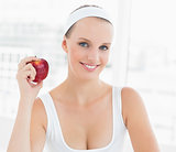 Smiling pretty sportswoman holding an apple