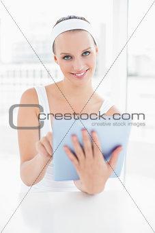 Calm pretty sportswoman using a tablet pc