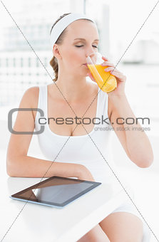 Peaceful pretty sportswoman drinking orange juice