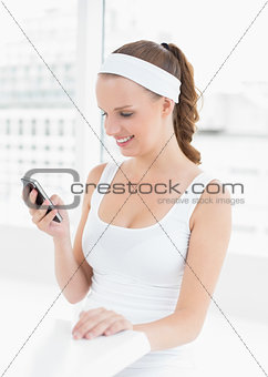 Calm pretty sportswoman using her mobile phone