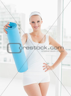 Relaxed pretty sportswoman holding her mat