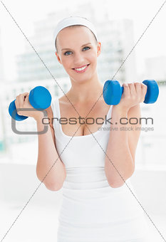 Motivated pretty sportswoman carrying dumbbells