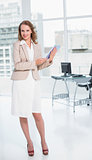 Happy pretty businesswoman holding a tablet pc