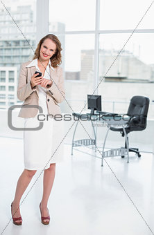 Joyful pretty businesswoman using her mobile phone