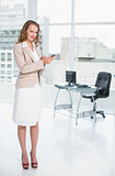 Content pretty businesswoman holding a mobile phone
