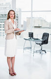 Smiling pretty businesswoman holding laptop