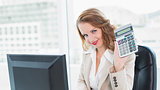 Relaxed pretty businesswoman holding a calculator