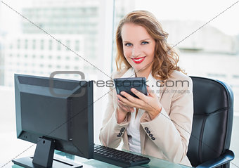 Calm pretty businesswoman using a calculator
