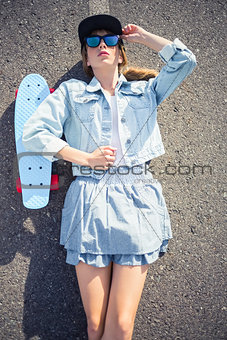 Rebellious blonde skater lying on the highway