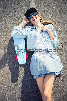 Smiling blonde skater lying on the highway