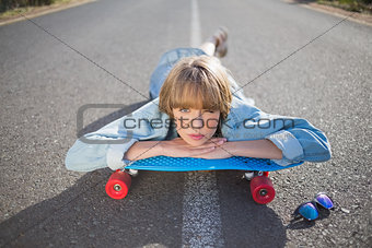 Funky young blonde lying on a road winking at camera