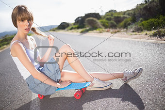 Pouting funky blonde sitting on her skateboard