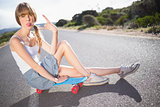 Funky blonde sitting on her skateboard making rock and roll hand gesture