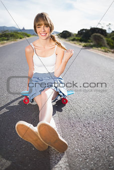 Cool skater girl doing sitting on her skateboard
