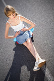 Trendy young woman sitting on her skateboard
