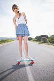 Peaceful trendy woman balancing on her skateboard