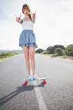 Trendy woman making rock and roll gesture while balancing on her skateboard