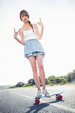 Young woman making rock and roll gesture while balancing on her skateboard