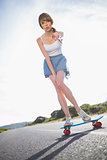 Young woman pointing at camera while balancing on her skateboard