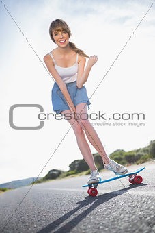 Cheerful young woman balancing on her skateboard