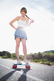Happy young woman balancing on her skateboard
