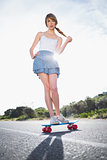 Astonished young woman balancing on her skateboard