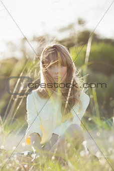 Blonde hipster girl sitting on the grass looking at camera