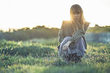 Fashionable young girl crouching in sheer dress and jacket