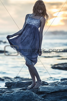 Beautiful young woman standing on rocks by the sea