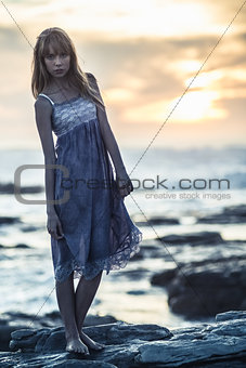 Beautiful model standing on rocks by the sea