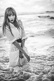 Beautiful model in shirt dress standing in the sea
