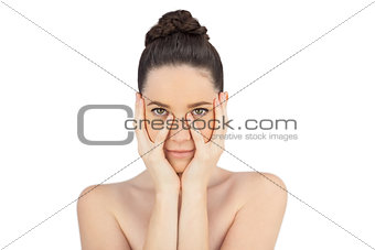 Natural model holding her face