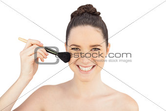Smiling sensual model using blusher brush