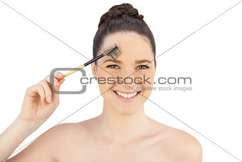 Smiling sensual model using eyebrow brush