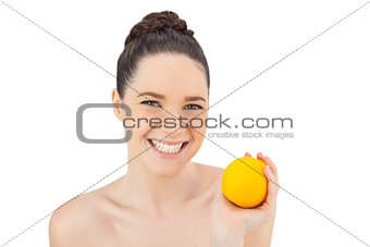 Cheerful pretty model holding orange