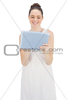 Smiling young model in white dress using tablet computer