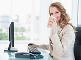 Smiling pretty businesswoman drinking coffee