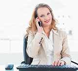 Pleased pretty businesswoman answering a phone call