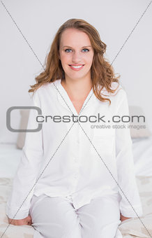 Smiling pretty woman sitting on her bed