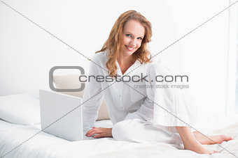 Content pretty woman using a laptop sitting on her bed