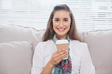 Smiling pretty model holding mug of coffee