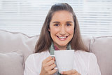 Smiling pretty model holding cup of coffee