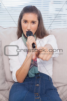 Gorgeous model pointing at camera singing on microphone