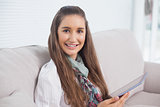 Smiling attractive brunette holding tablet computer