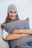 Smiling pretty brunette with winter hat on posing