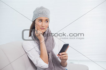 Thoughtful pretty brunette with winter hat on holding her phone