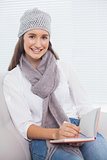 Smiling pretty brunette with winter hat on writing on her notebook