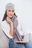 Thoughtful pretty brunette with winter hat on holding notebook