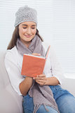 Happy pretty brunette with winter hat on writing on notebook