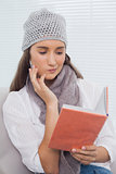Thoughtful brunette with winter hat on holding notebook